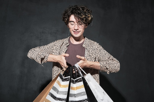 Junger modedesigner, der einkaufstüten in den händen vor dem schwarzen hintergrund hält