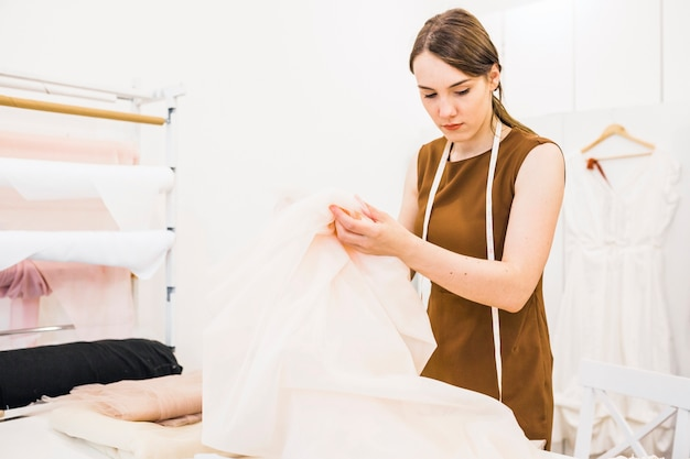Junger modedesigner, der gewebe im shop wählt