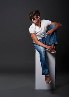 Junger modemann, der auf weißem rechteck sitzt