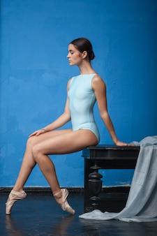 Junger moderner balletttänzer, der auf blau aufwirft