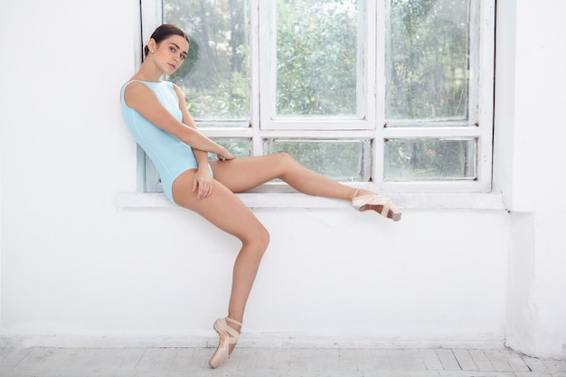 Junger moderner balletttänzer, der auf weißer wand aufwirft