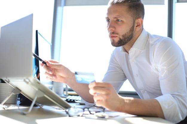 Junger moderner geschäftsmann, der daten mit laptop analysiert, während er im büro arbeitet.