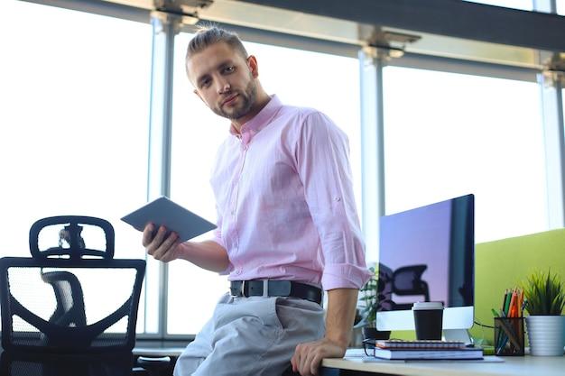 Junger moderner geschäftsmann, der mit digitalem tablet arbeitet, während er im büro sitzt.