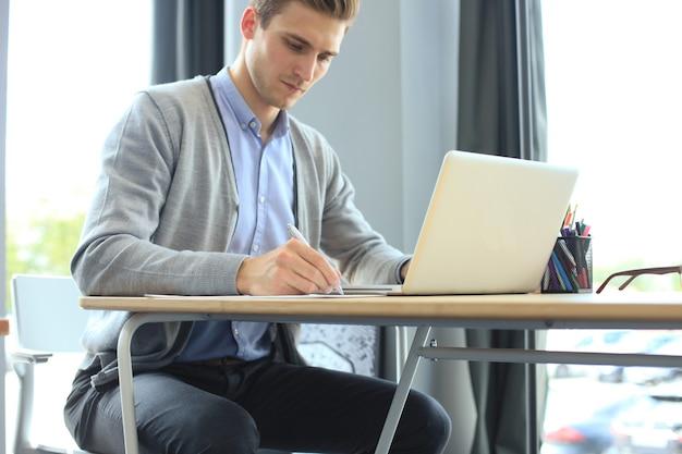Junger moderner geschäftsmann, der mit laptop arbeitet, während er im büro sitzt