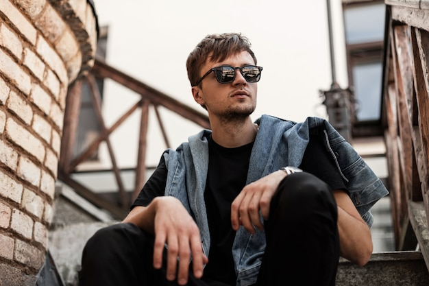 Junger moderner hipster-mann in einer modischen jeansjacke in schwarzen hosen in stilvoller dunkler sonnenbrille entspannen sich sitzend auf einer vintage-treppe nahe ziegelmauer in der stadt. cooler typ genießt ein wochenende im freien.