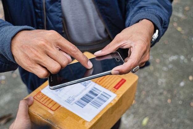 Junger moderner lieferer, der smartphone auf lieferungsarbeitszeit verwendet.