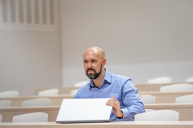 Junger moderner mann auf einer universitätsvorlesung, die an einem laptop arbeitet