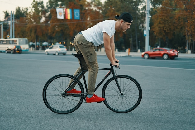 Junger moderner mann, der auf einem klassischen fahrrad auf der stadtstraße radelt