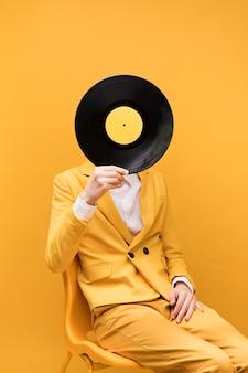 Junger moderner mann, der vinyl vor gesicht hält