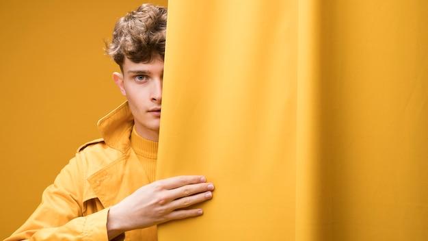 Junger moderner mann hinter vorhang