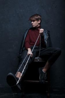 Junger moderner mann in einer modischen jacke im vintage-burgundergolf in trendigen jeans und schwarzen turnschuhen mit einer metallkette sitzt auf einem holzstuhl in einem raum nahe einer schwarzen wand. hübscher stilvoller kerl