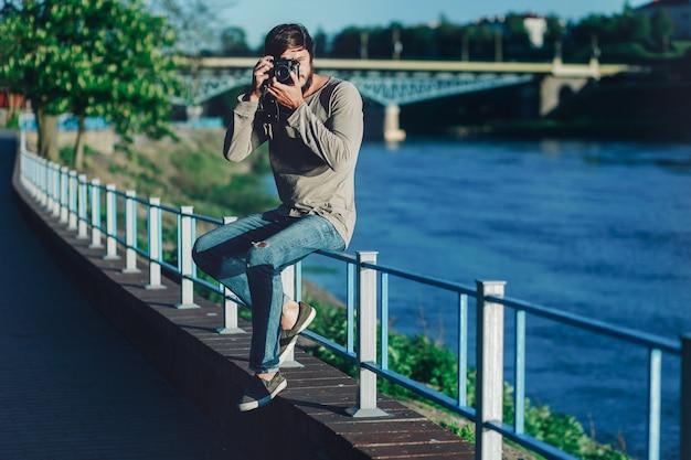 Junger moderner mann macht ein foto mit einer alten retro- kamera im park