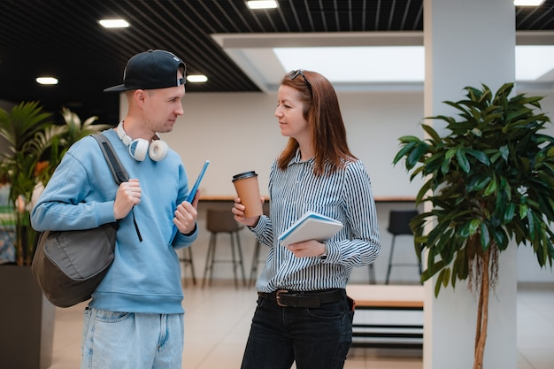 Junger moderner modischer mann und frau besprechen ein gemeinsames projekt im büro