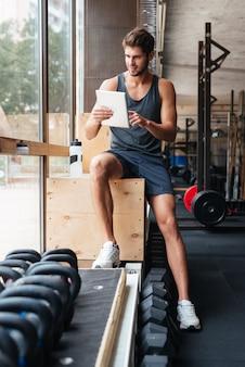 Junger modesportler im fitnessstudio. mit tablet