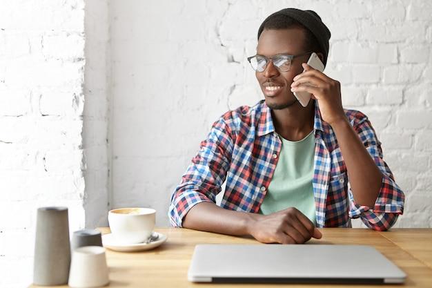 Junger modischer kerl, der an einem café mit smartphone sitzt