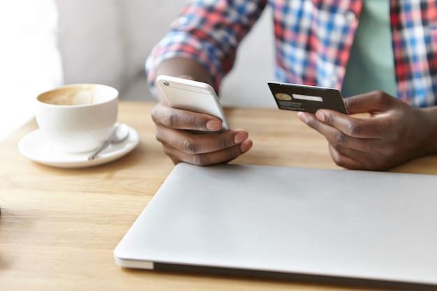 Junger modischer kerl, der an einem café mit smartphone und laptop sitzt