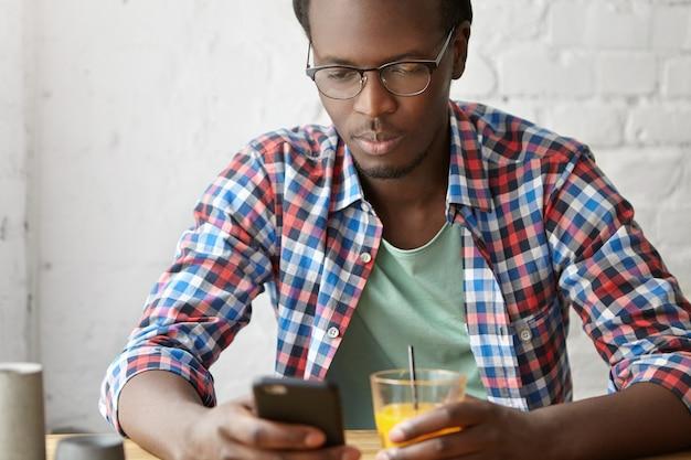Junger modischer kerl, der an einem café mit telefon sitzt