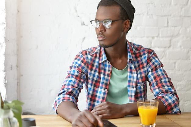 Junger modischer kerl, der an einem café sitzt
