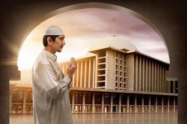 Junger moslemischer asiatischer mann, der zum gott betet