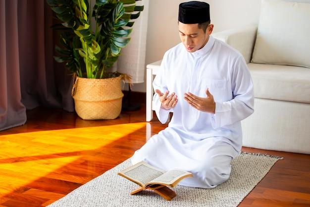 Junger moslemischer mann, der allah traditionelles gebet macht