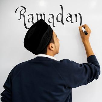 Junger moslemischer mann, der ramadan auf ein whiteboard schreibt
