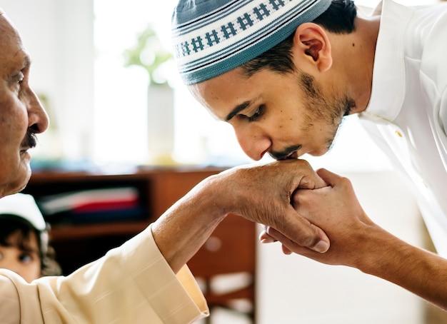 Junger moslemischer mann, der seinem vater respekt zeigt