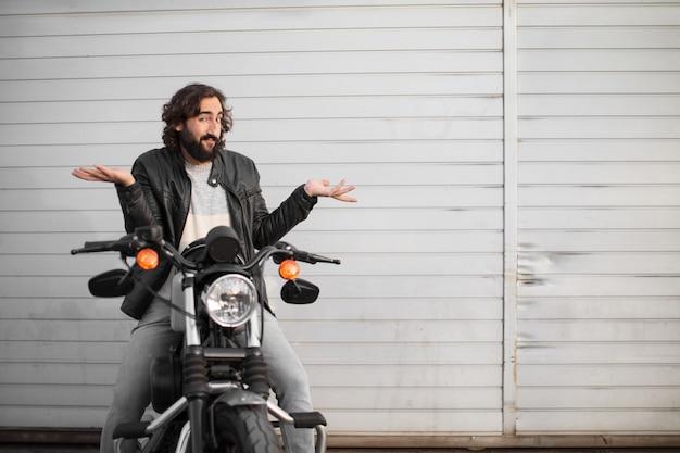 Junger motorradfahrer auf seinem weinlesefahrrad