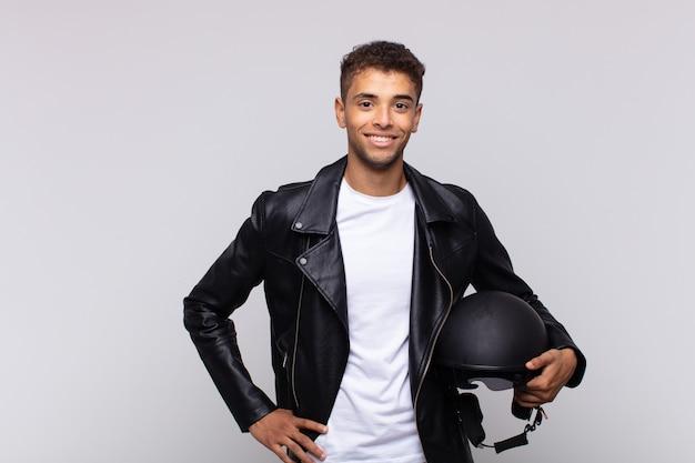 Junger motorradfahrer, der glücklich mit einer hand auf hüfte und selbstbewusster, positiver, stolzer und freundlicher haltung lächelt