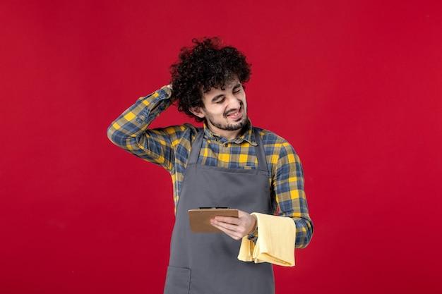 Junger müder männlicher server mit lockigem haar, der ein handtuch hält, das die bestellung auf isoliertem rotem hintergrund aufnimmt