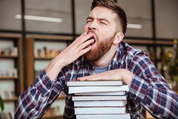 Junger müder männlicher student, der gähnt, während er an der bibliothek sitzt