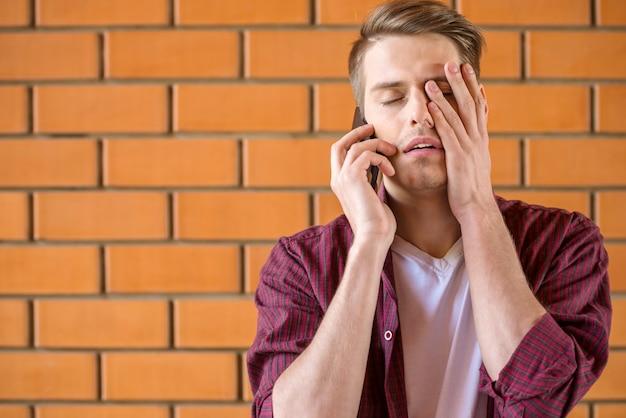 Junger müder mann, der am telefon auf backsteinmauer spricht