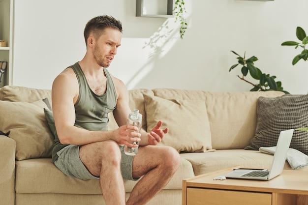 Junger müder sportler mit einer flasche wasser, die auf der couch nach dem training sitzt und durch video-chat vor laptop im wohnzimmer spricht