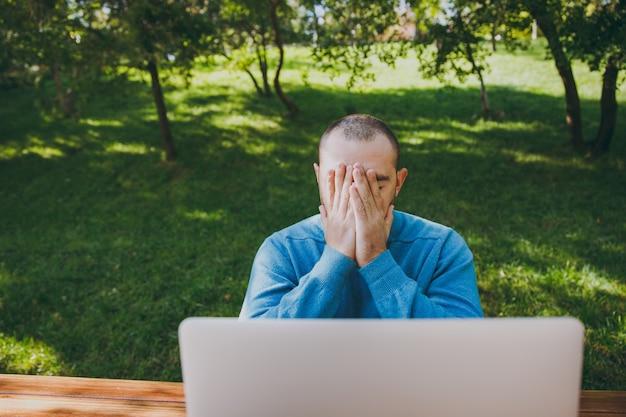 Junger müder trauriger mann geschäftsmann oder student in lässigem blauem hemd, brille sitzt am tisch mit handy im stadtpark mit laptop, arbeitet im freien, macht sich sorgen um probleme. mobile office-konzept.
