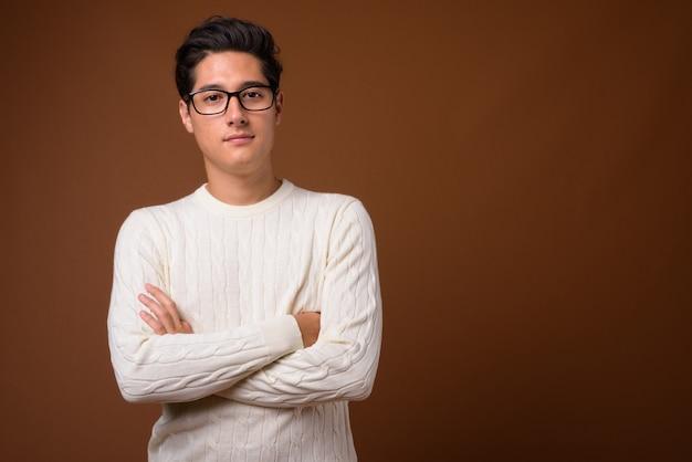 Junger multiethnischer schöner mann gegen braunen hintergrund