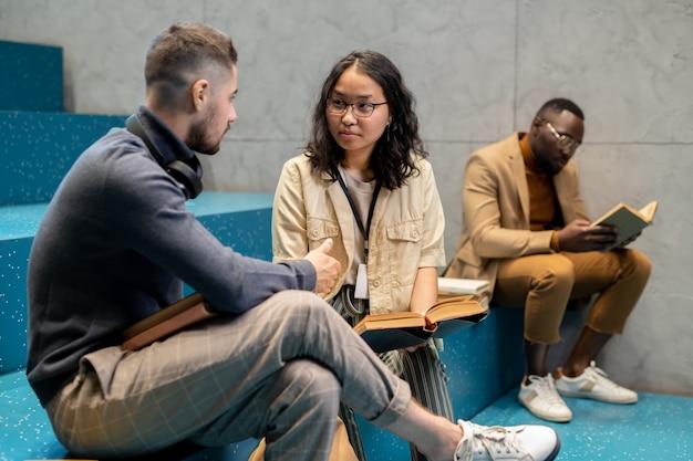 Junger multikultureller mann und frau mit büchern, die in der pause interagieren