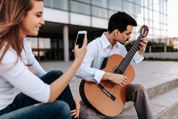Junger musiker, der akustikgitarre in der stadt spielt, während an einem telefon von einem mädchen notiert wird.