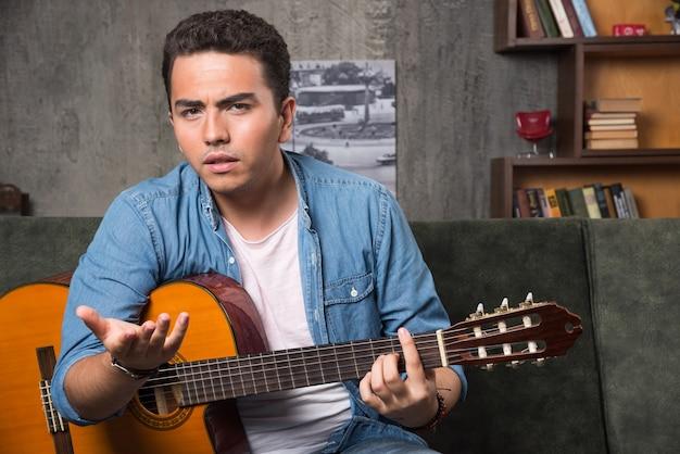 Junger musiker, der eine schöne gitarre hält und auf sofa sitzt. hochwertiges foto