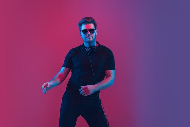Junger musiker, der im neonlicht singt und tanzt