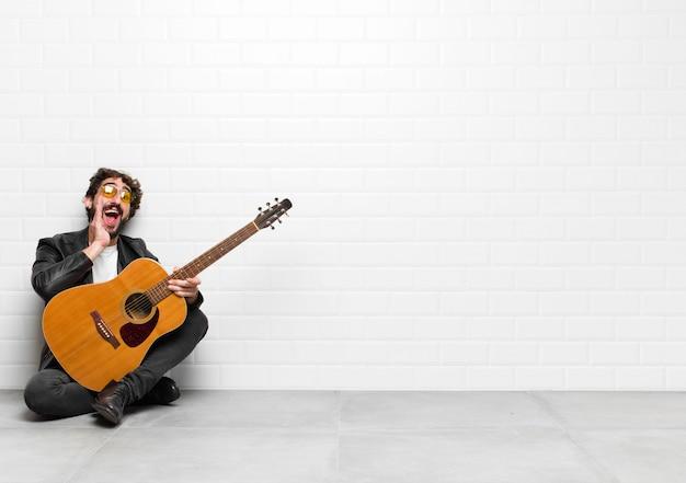 Junger musiker mann, der glücklich, aufgeregt und positiv fühlt, einen großen schrei mit den händen neben dem mund gibt und mit einem gitarren-, rock'n'roll-konzept ruft