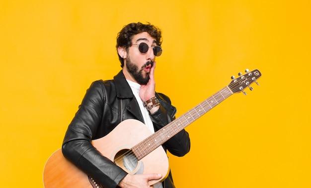 Junger musiker mann, der sich schockiert und erstaunt fühlt gesicht zu hand im unglauben mit weit geöffnetem mund mit einem gitarren-, rock'n'roll-konzept