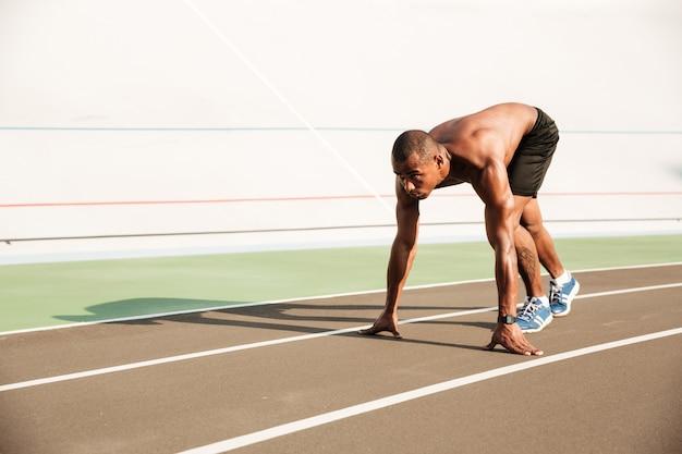 Junger muskulöser afrikanischer sportmann in der startposition bereit zu starten
