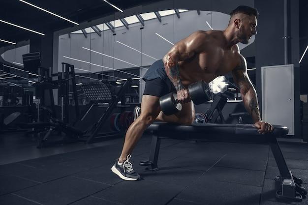 Junger muskulöser athlet, der im fitnessstudio mit den gewichten übt