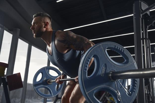Junger muskulöser athlet, der klimmzüge im fitnessstudio mit langhantel übt