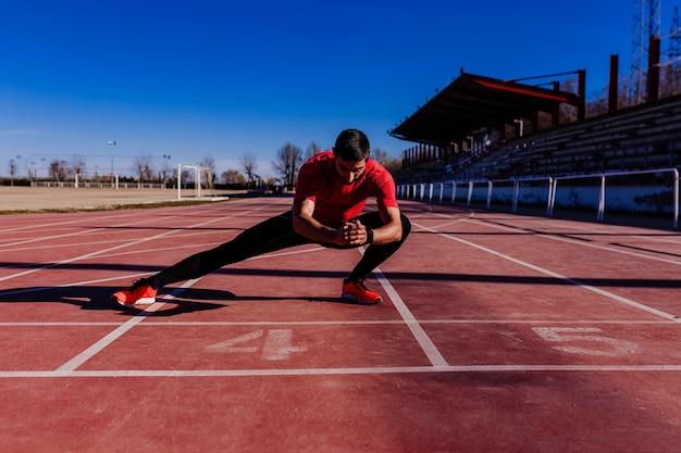 Junger muskulöser athlet ist am anfang der rennstreckenlinie am stadion. sport-konzept