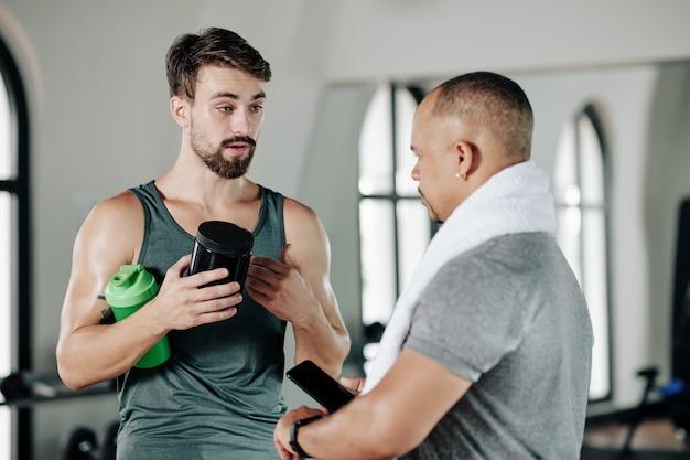 Junger muskulöser fitnesstrainer, der dem kunden proteine und nahrungsergänzungsmittel empfiehlt