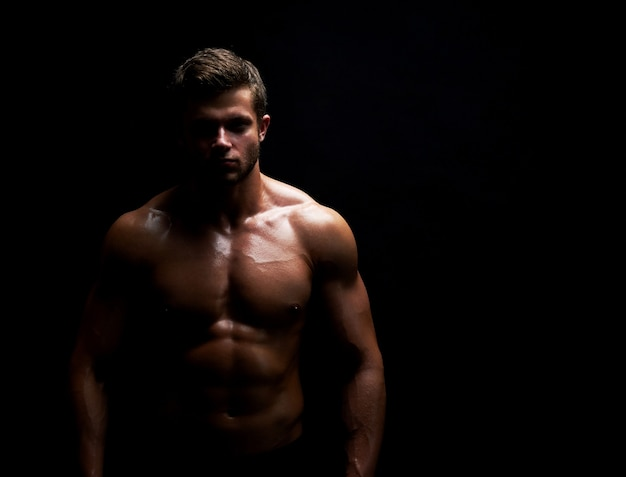 Junger muskulöser fitter sportler posiert mit nacktem oberkörper