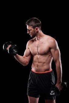 Junger muskulöser hemdloser gewichtheber in kurzen hosen, die übung für arme mit hanteln über schwarzer wand tun