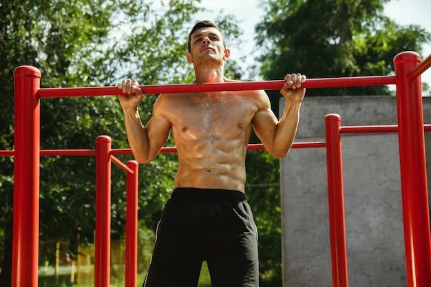 Junger muskulöser hemdloser kaukasischer mann, der klimmzüge auf horizontaler stange am spielplatz am sonnigen sommertag tut. trainiere seinen oberkörper im freien. konzept von sport, training, gesundem lebensstil, wohlbefinden.