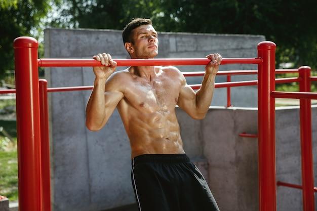 Junger muskulöser hemdloser kaukasischer mann, der klimmzüge auf horizontaler stange am spielplatz am sonnigen sommertag tut