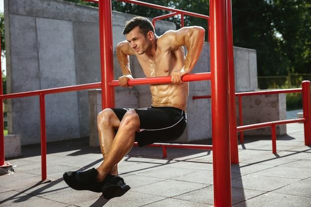 Junger muskulöser hemdloser kaukasischer mann, der klimmzüge auf horizontaler stange tut